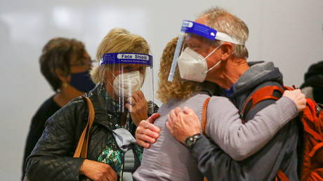 Travelers wearing protective face masks and face shields to prevent the spread of the coronavirus disease (COVID-19) hug at the airport in Denver, Colorado, U.S., (FILE PHOTO) © REUTERS/Kevin Mohatt