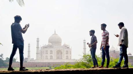 People take pictures with their mobile phones near the Taj Mahal in Agra on September 8, 2020. © AFP / Pawan Sharma