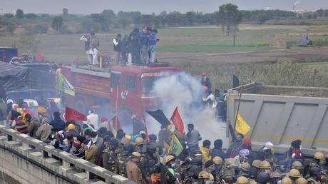 Farmers run as police fire tear gas shells near Ambala, India, November 26, 2020 © REUTERS/Stringer