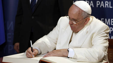 FILE PHOTO: Pope Francis signs the golden book during a ceremony at the European Parliament in Strasbourg. © Pool via Reuters / Christophe Karaba