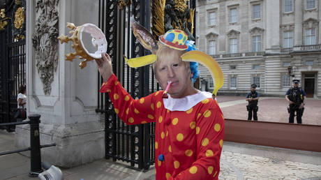 Anti Brexit protester dressed up as a clown version of Prime Minister Boris Johnson hires a 'Boris' bike in Westminster and cycles to the gates of Buckingham Palace.