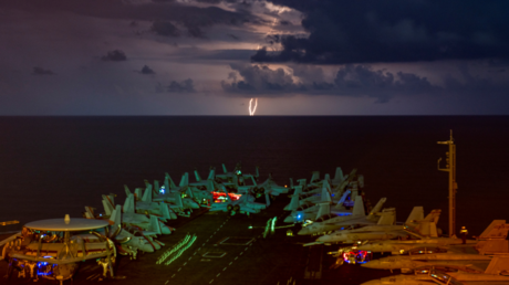 FILE PHOTO: Lightning flashes over the US Navy aircraft carrier USS Nimitz on July 4, 2020