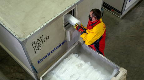 "A DHL worker loads dry ice into ""Envirotainers"" inside an ultra-cold facility that is used for the shipment of vaccines, medical supplies and pharmaceuticals in Chicago, Illinois, US, in this handout photo released on November 18, 2020. © Reuters / DHL"