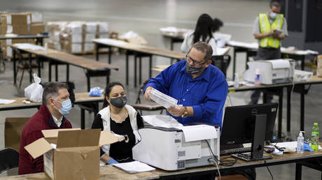 Workers scan ballots as the Fulton County presidential recount gets under way Wednesday morning, Nov. 25, 2020 at the Georgia World Congress Center in Atlanta © AP Photo/Ben Gray