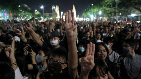 Thailand's King calls for unity after protesters turn back on his motorcade & throw up 'Hunger Games' salute (VIDEOS, PHOTOS)