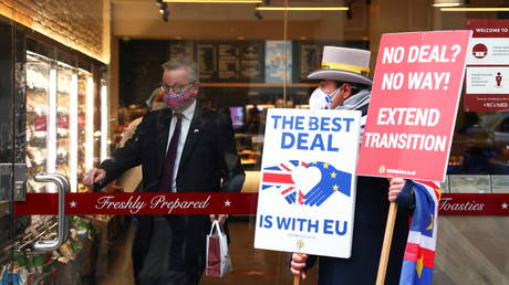 Britain's Chancellor of the Duchy of Lancaster Michael Gove leaves a coffee shop as an anti-Brexit protestor stands outside, in London, Britain, November 30, 2020. © Reuters / Simon Dawson