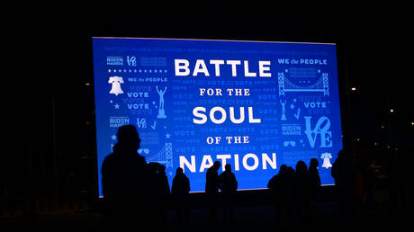 "FILE PHOTO: Attendees are silhouetted in front a digital screen displaying a campaign message stating ""BATTLE FOR THE SOUL OF THE NATION"" before Democratic vice presidential nominee Sen. Kamala Harris (D-CA) speaks at a drive-in election eve rally on November 2, 2020 in Philadelphia, Pennsylvania"