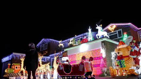 A person looks at a house displaying Christmas lights in Hemel Hempstead, UK