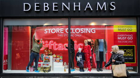 Members of staff attach a closing down sign in a window of Debenhams store, amid the outbreak of the coronavirus disease (COVID-19) in Manchester, Britain, December 2, 2020