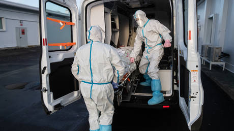 """Medical workers during the transportation of a patient on the territory of the hospital in the intensive care unit in the hospital for patients with COVID-19 in the Moscow clinical center for infectious diseases """"Voronovskoe""""."""