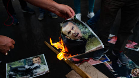 People burn caricatures of French President Emmanuel Macron during a demonstration in Istanbul, Turkey. October 2020. © Yasin Akgol / AFP