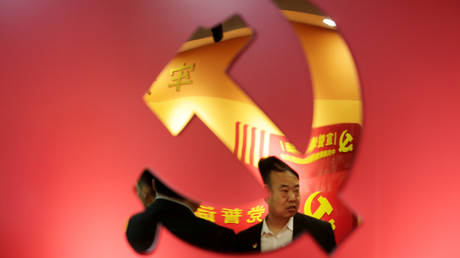 FILE PHOTO: Party members are reflected on a party emblem of the Communist Party of China (CPC) at Tidal Star Group's party activity room in Beijing, China, February 25, 2019