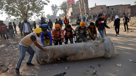 Farmers push a cement pipe to use it as a roadblock during a protest against the newly passed farm bills at Singhu border near Delhi, India, November 28, 2020. © Reuters / Danish Siddiqui