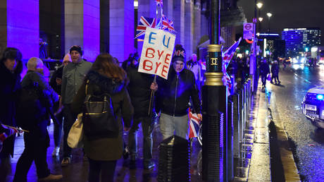 "FILE PHOTO: A pro Brexit supporters arrives holding a placard saying ""EU Bye Bye"" for the Leave Means Leave, Brexit day celebration party outside the Houses of Parliament at Parliament Square on January 31, 2020 in London, England"
