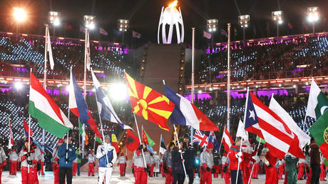 FILE PHOTO: People carry national flags during closing ceremony of Olympic Games in Pyeongchang, South Korea. February 2018. © Reuters / Lucy Nicholson