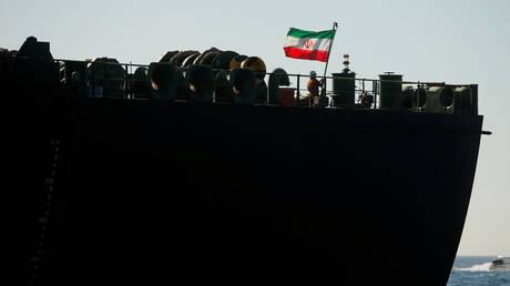 A crew member raises the Iranian flag on Iranian oil tanker