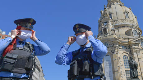 German police with protective masks patrol at the Neumarkt square in Dresden, Germany, April 20, 2020.