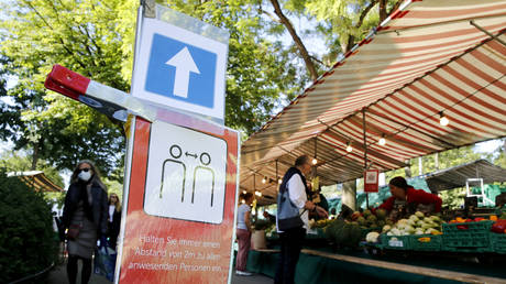"FILE PHOTO: A sign reading: ""Always keep a distance of 2 meters from all persons present"" is seen in front of a stall at a weekly market in Zurich, Switzerland."
