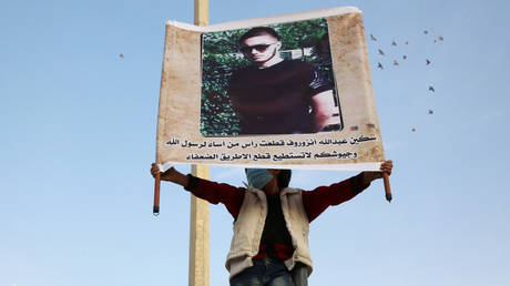 FILE PHOTO A Syrian demonstrator raises a portrait of Abdullakh Anzorov, an 18-year-old ethnic Chechen who beheaded a French teacher near Paris, the rebel-held northeastern city of Idlib on October 28, 2020. ©  AFP / Mohammed AL-RIFAI