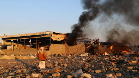 Smoke rises as people inspect damage at the site of air strikes in the city of Saada, Yemen