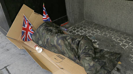 FILE PHOTO: A homeless person lays on cardboard decorated with Union Flags in central London.