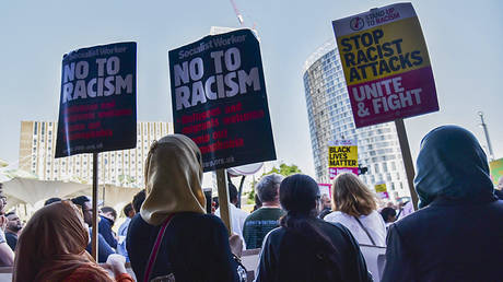 """FILE PHOTO: Protesters hold banners reading """"No To Racism..."""" in London, UK © Getty Images/Ray Tang/Anadolu Agency"""
