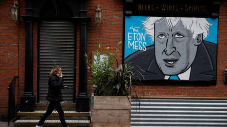 A woman walks past a caricature of Britain's Prime Minister Boris Johnson in the boarded up window of a closed pub in Manchester, Britain, (FILE PHOTO) © REUTERS/Phil Noble