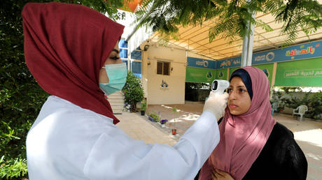 A Palestinian healthcare worker checks resident's body temperature amid a coronavirus outbreak in Gaza. © Reuters / Mohammed Salem