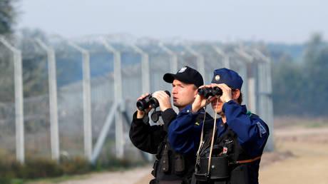Hungarian and Polish policeman patrol at the Hungary and Serbia border fence (FILE PHOTO) © REUTERS/Laszlo Balogh