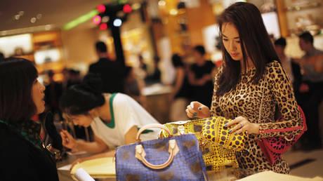 FILE PHOTO: A woman shops in a Louis Vuitton store in downtown Shanghai ©Reuters / Carlos Barria