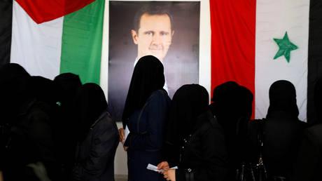 PHOTO DE DOSSIER: Les femmes se lèvent en attendant leur tour pour voter à l'intérieur d'un bureau de vote lors des élections législatives à Douma, dans la banlieue est de Damas, en Syrie, le 19 juillet 2020