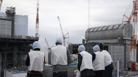 FILE PHOTO. Journalists inspect Unit 2 (L) and Unit 3 (R) reactors during their tour at tsunami-devastated Fukushima Daiichi Nuclear Power Plant.