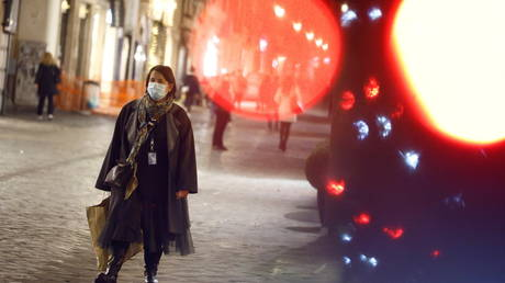 FILE PHOTO: A woman walks along a shopping street ahead of Christmas amid the spread of the coronavirus in Rome, Italy.