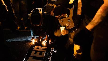 Proud Boys leader Enrique Tarrio (right of center) and others attempt to set fire to a Black Lives Matter banner during a rally in Washington, DC, December 12, 2020.