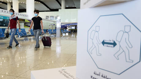 FILE PHOTO: Travellers wearing protective face masks walk at Riyadh International Airport © REUTERS/Ahmed Yosri