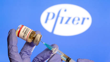 "FILE PHOTO: A woman holds a small bottle labeled with a ""Coronavirus COVID-19 Vaccine"" sticker and a medical syringe in front of displayed Pfizer logo in this illustration taken, October 30, 2020."