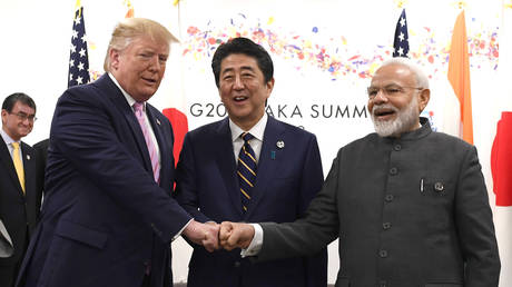 FILE PHOTO: US President Donald Trump does a fist bump with Japan's then-Prime Minister Shinzo Abe and Indian Prime Minister Narendra Modi during the G20 summit in Osaka, Japan.