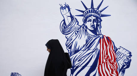 FILE PHOTO: A woman walks in front of new murals of the former US embassy in Tehran, Iran November 2, 2019