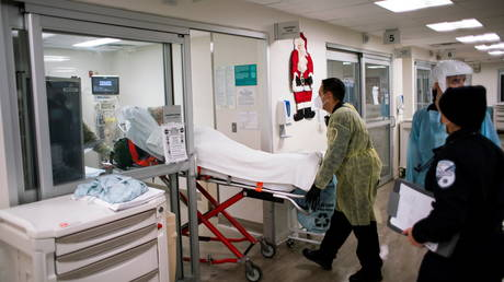 FILE PHOTO. A coronavirus patient is transported into the emergency room at a hospital in New Jersey, US.