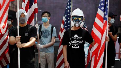 Des manifestants anti-gouvernementaux tiennent des drapeaux américains lors d'un rassemblement à l'Université de Hong Kong, Chine, en septembre 2019. © Jorge Silva / Reuters