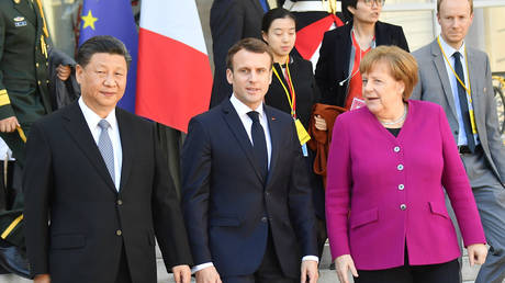 FILE PHOTO: French President Emmanuel Macron (C) accompanies Chinese President Xi Jinping (L) and German Chancellor Angela Merkel (R) after their meeting at the Elysee Presidential Palace on March 26, 2019 in Paris