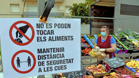 Covid-19 warning signs at a market in Spain