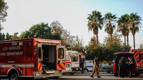 Firefighters and paramedics wait outside LAC + USC Medical Center during a surge of coronavirus cases in Los Angeles, California, December 27, 2020.