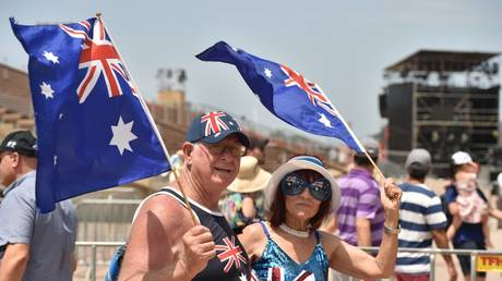 FILE PHOTO: People wave the Australian flag to celebrate Australia Day in Sydney on January 26, 2020 © AFP / Peter Parks