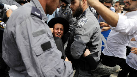 FILE PHOTO: An ultra-Orthodox Jewish man being arrested by police during protests. © Reuters / Ammar Awad