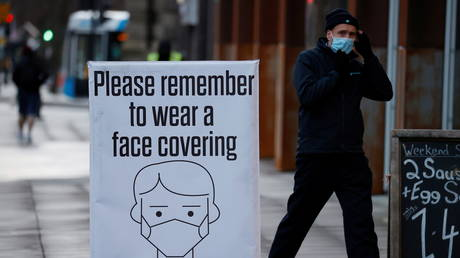 FILE PHOTO: A man walks past a sign encouraging people to wear face coverings amid the COVID-19 outbreak in Belfast, Northern Ireland. © REUTERS / Phil Noble