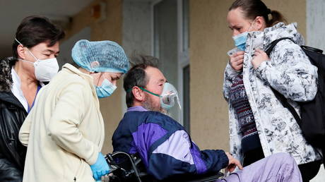 FILE PHOTO: A medical specialist assists a patient outside a hospital for people infected with the coronavirus disease (COVID-19) in Kyiv, Ukraine November 24, 2020.