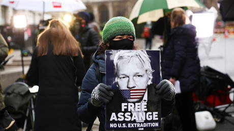 A supporter of WikiLeaks founder Julian Assange holds a placard, at the Old Bailey, the Central Criminal Court, in London, Britain, January 4, 2021.