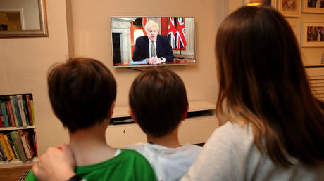 FILE PHOTO: A family in Knutsford, Cheshire, watch Prime Minister Boris Johnson making a televised address to the nation from 10 Downing Street, London, setting out new emergency measures to control the spread of coronavirus in England.