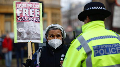 A woman holding a placard looks at a police officer outside at the Westminster Magistrates Court ahead of a hearing as Assange's lawyers seek bail for their client in London, Britain January 6, 2021.
